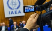 "A cameraman films a podium with officials and a large logo saying ""IAEA"""
