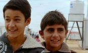 "Two boys outside in a desert refugee camp walking towards the camera. Credit: ""After Spring"" Movie Facebook page."