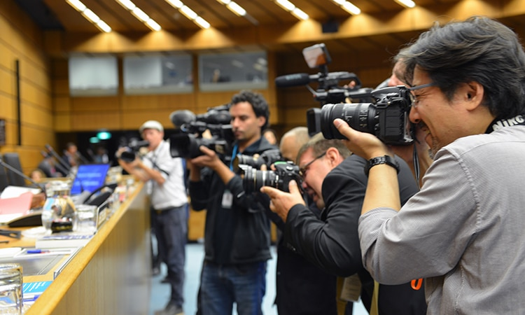 A group of reporters taking pictures in a large meeting room.